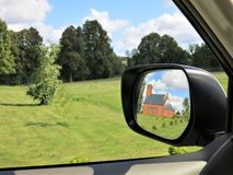 Side mirror car rear view. With the reflection in it of the lutheran church Royalty Free Stock Photography
