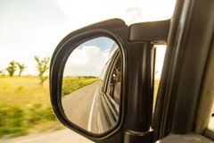 Side mirror on the car on the road.  Stock Image