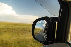 Side mirror on the car on the road.  Royalty Free Stock Photography