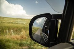 Side mirror on the car on the road.  Royalty Free Stock Image