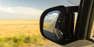 Side mirror on the car on the road.  Stock Photos