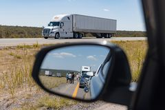 Side mirror on car shows view of motorists stranded Massive traffic pile up on interstate 40 new mexico. People wait impatiently for road block to clear after stock images