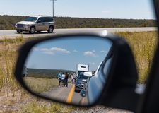 Side mirror on car shows view of motorists stranded Massive traffic pile up on interstate 40 new mexico. People wait impatiently for road block to clear after royalty free stock images