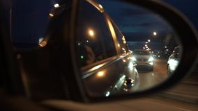 Side mirror rear view from moving car at night. Royalty Free Stock Photo