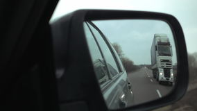 Side mirror view of passing the truck on highway. Car overtakes the truck on interurban highway. POV view to the side mirror of the car. Overtaking maneuver slow stock video