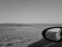 Side mirror view of windmill and truck Royalty Free Stock Photos