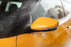 Side mirror of yellow car being washed in self service carwash, stock photo
