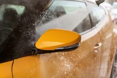 Side mirror of yellow car washed in self service carwash, jet sp stock images