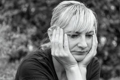 Side monochrome portrait of a frustrated middle aged woman. Who is supporting her face by hands and is looking ahead Royalty Free Stock Photo