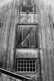 Side of old dirty white New England Barn during a mid-December snow storm. Snowing, hay door, 2 windows Stock Images