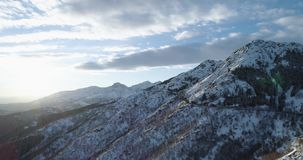 Side orbit aerial top view on white snow mountain in winter.Forest woods.Snowy mountains street path establisher.Sunset. Or sunrise sun backlit.4k drone flight stock video