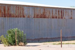 Side of a partially rusted metal building stock image