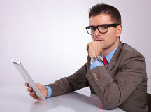 Side of pensive young business man with tablet looking at you Royalty Free Stock Photography