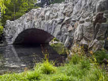 Side Perspective of stone bridge over the water in beacon hill park. A Beautiful old stone bridge across a pond in the heart of beacon hill park - Victoria BC Stock Photos