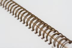 Open notebook with metal spiral closeup detail. Side perspective view closeup of open notebook with copper metal spirals and blank white pages stock photography
