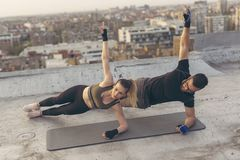 Side plank exercise. Couple working out on a building rooftop terrace, doing a side plank exercise royalty free stock image
