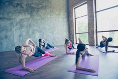 Side plank exercise. Five concentrated sporty girls are doing pl royalty free stock photo