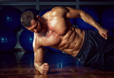 Side plank exercise. Man doing side plank exercise in gym Royalty Free Stock Photography
