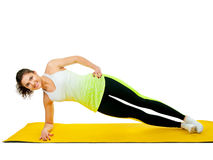 Side plank exercise. Sports girl doing side plank on a yellow sport mat royalty free stock photos