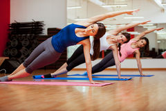 Side plank yoga pose by three women Royalty Free Stock Images