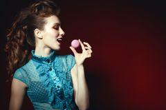Side portrait of a beautiful model with creative hairstyle and colourful make up holding violet macaroon with an open mouth royalty free stock image