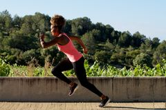 Black woman sprinting outdoors. Side portrait of black woman sprinting outdoors Stock Photography