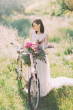 The side portrait of the bride in long white dress standing near the bycicle with the flower bouquet in the sunny green. Field Royalty Free Stock Images