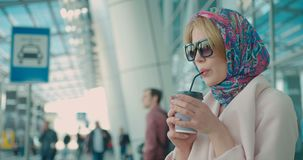 Side portrait of the charming fashionable blonde woman wearing scarf on head and sunglasses. She is drinking coffee via. The tubule from the paper glass near stock video footage