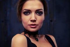 Side portrait of classy elegant woman in black eveningwear posing in dark studio background royalty free stock image