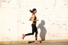 Side portrait of fit young woman running outdoors. Full length side portrait of fit young woman running outdoors Stock Images