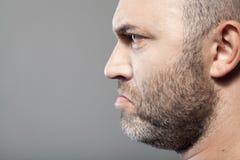 Side portrait of gloomy man isolated on gray Stock Photos