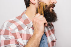 Side portrait of handsome caucasian man with funny mustache smile and comb his big Stock Image