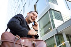 Side of happy travel man talking on cellphone in the city. Side portrait of happy travel man talking on cellphone in the city royalty free stock photo