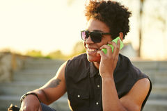 Side portrait of a happy young man using mobile phone outside. royalty free stock image