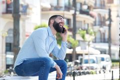 Side of laughing man sitting outside talking on mobile phone Royalty Free Stock Photography