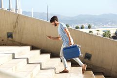 Side portrait of male traveler with suitcase and mobile phone. Full length side portrait of male traveler with suitcase and mobile phone Stock Photography