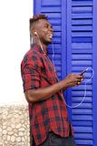 Side of smiling african man with mobile phone and headphones standing outside. Side portrait of smiling african man with mobile phone and headphones standing Stock Images