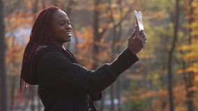 The side portrait of the smiling afro-american girl taking selfie in the autumn park. stock footage