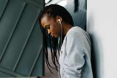 Side portrait of the smiling young afro-american girl in the earphones standing near the wall. Stock Photos