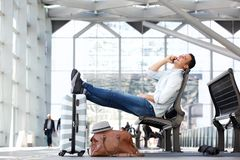Travel man talking on cellphone while waiting with suitcase and bags at station. Side portrait of travel man talking on cellphone while waiting with suitcase and royalty free stock image