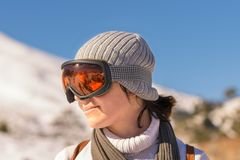Side portrait of a woman against the snow wearing snow glasses. Stock Photos