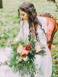 The side portrait of the woman with long curly hair in the white wedding dress, holding the colourful bouquet and. Sitting on the chair in the spring green Stock Photo