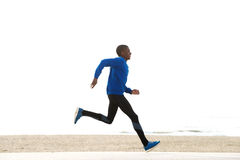 Side portrait of young african american man running by the beach Royalty Free Stock Images