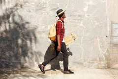 Side portrait of young african american man walking outside with skateboard. Full length side portrait of young african american man walking outside with stock images