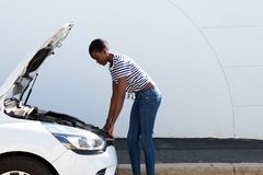 Young african american woman looking under the hood of broken down car. Side portrait of young african american woman looking under the hood of broken down car Royalty Free Stock Photography