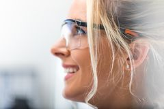 Side portrait of young attractive woman in protective eyeglasses. Closeup macro side view profile portrait of the young attractive happy smiling woman in stock photo