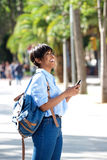 Side portrait young black woman walking outside with mobile phone stock photography