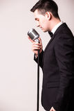 Side portrait of young man in suit singing with the microphone Royalty Free Stock Photos