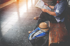 Side portrait of a  young man traveler sitting with map choose w Stock Images
