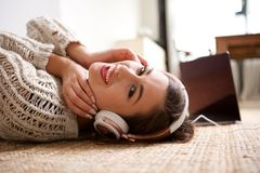 Young woman lying on floor and smiling with headphones. Side portrait of young woman lying on floor and smiling with headphones Royalty Free Stock Photos